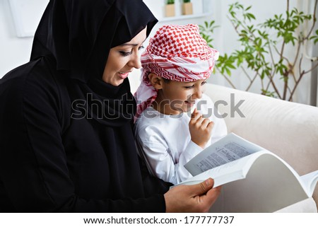 Happy Arabic mother and son together sitting on the couch and reading a book. - stock photo