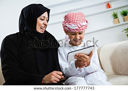 Happy Arabic mother and son together sitting on the couch and using digital tablet. - stock photo