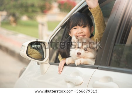 Happy asian asian girl and siberian husky puppy sitting in the car - stock photo