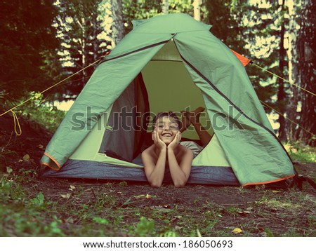 happy asian boy in camping tent in summer forest - vintage retro style  - stock photo