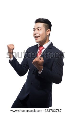 Happy asian businessman celebrating his success on white background. Looking side - stock photo