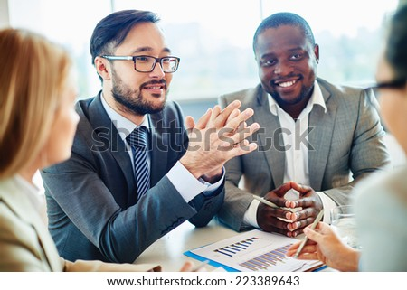 Happy Asian businessman looking at colleague during discussion - stock photo