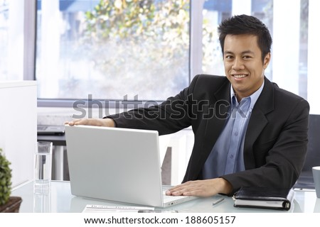 Happy Asian businessman sitting at desk, working with laptop computer, smiling, looking at camera. - stock photo