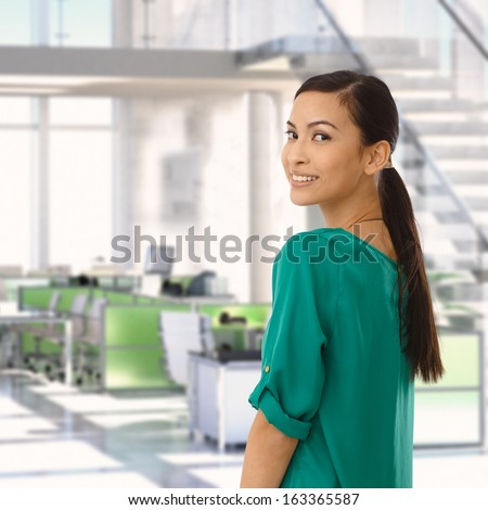 Happy asian businesswoman at office looking back over the shoulder, smiling. - stock photo