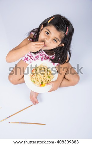Happy Asian child eating delicious noodle, cheerful little indian girl posing with noodles in white dish isolated over white background, girl eating noodles, top view - stock photo