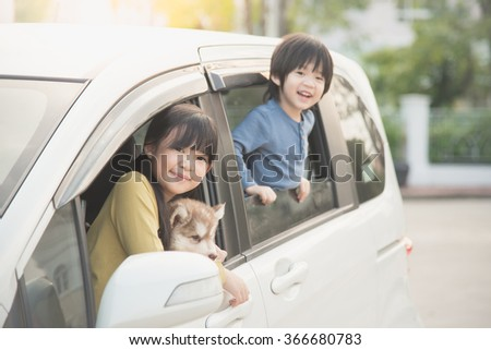 Happy asian children and siberian husky puppy sitting in the car - stock photo