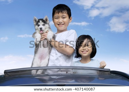 Happy Asian children standing on the sunroof of the car while holding siberian husky puppy and smiling at the camera - stock photo