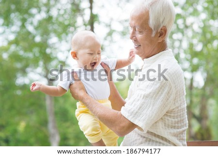 Happy Asian Chinese grandpa and grandson having fun at outdoor garden. - stock photo