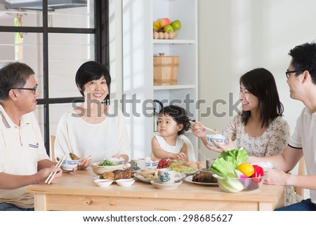 Happy Asian Chinese multi generations family dining at home. Eating with chopsticks. - stock photo