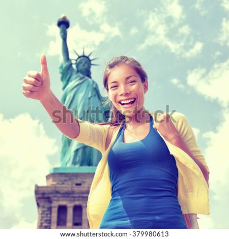 Happy Asian Chinese tourist doing thumbs up having fun visiting the Statue of Liberty, american landmark in New York City. Famous touristic attraction, USA. - stock photo