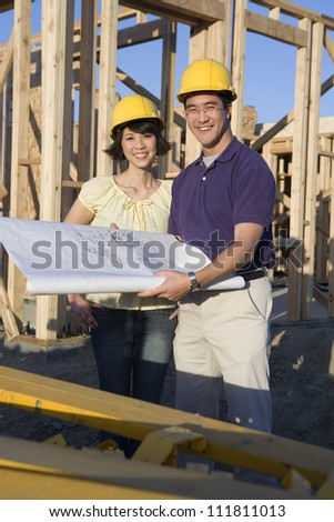 Happy asian couple at construction site - stock photo