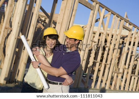 Happy asian couple with blueprint at construction site - stock photo