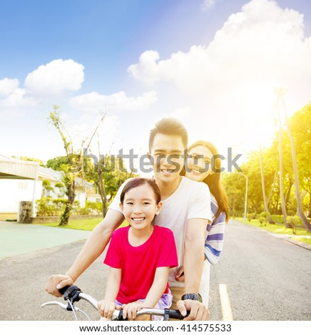 Happy asian family having fun in park with bicycle - stock photo