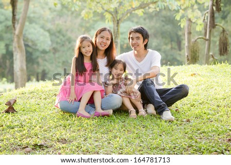 Happy Asian family in park - stock photo