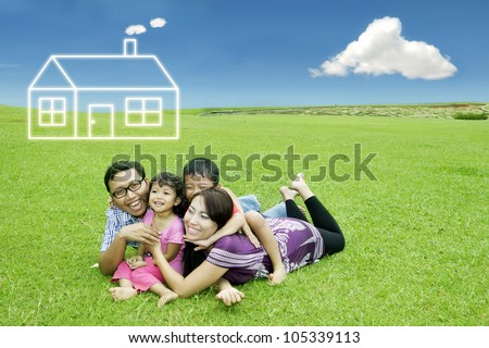 Happy asian family lying on the meadow with dream house - stock photo