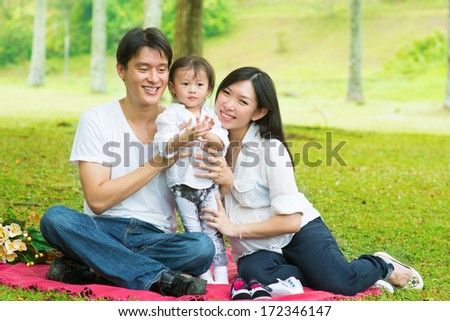 Happy Asian family outdoor activity. Parents and daughter having , picnic on garden green lawn. - stock photo