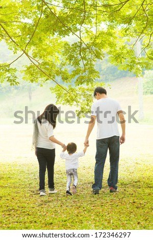 Happy Asian family outdoor activity. Rear view of parents and daughter having fun and walking on green lawn. - stock photo