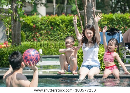 Happy Asian Family Playing in the pool - stock photo