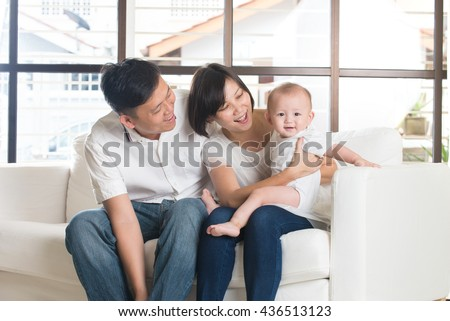 Happy Asian Family Playing with baby in the living room - stock photo