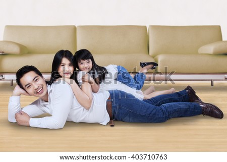 Happy Asian family relaxing together while lying on the floor at home and smiling at the camera - stock photo