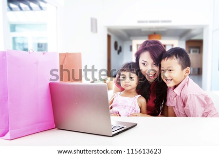 Happy asian family shopping online by using laptop computer, shot at home - stock photo