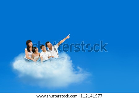 Happy Asian family sitting on cloud and pointing over blue sky - stock photo