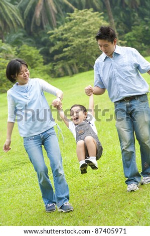 Happy Asian family walking in the park - stock photo