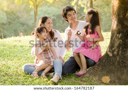 Happy Asian family with ice cream in park - stock photo