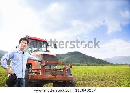 happy asian farmer with Old tractor on the grass field - stock photo