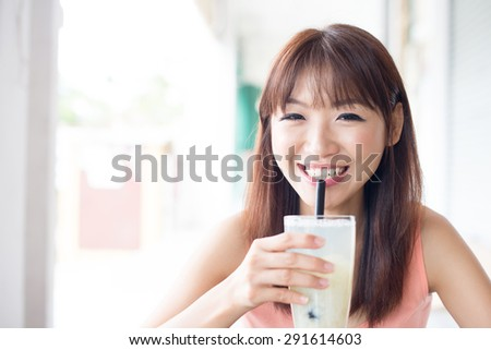 Happy Asian girl drinking a glass of beverage with straw in cafe. Young woman living lifestyle. - stock photo