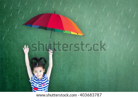 Happy asian girl kid raising hand holding colorful rainbow umbrella protect from rainy weather day on school grunge green school chalkboard background: Insurance protection safety health care concept - stock photo