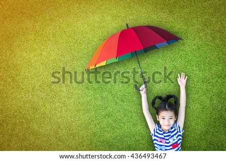 Happy asian girl kid raising hand lying on natural green grass lawn eco bio background holding colorful rainbow umbrella UV protection on sunny day: Insurance protection safety health care CSR concept - stock photo