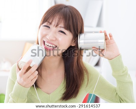 Happy Asian girl using old technology, talk and listen to communication cans. Young woman indoors living lifestyle at home. - stock photo