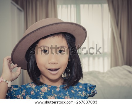 Happy Asian girl wearing hat and blue dress in room with vintage tone. - stock photo