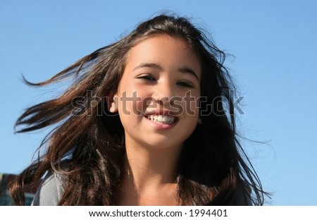 Happy asian girl with flowing hair - stock photo
