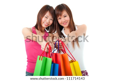 Happy Asian girls standing in shopping bags - stock photo