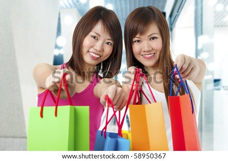 Happy Asian girls standing with shopping bags, shopping mall as background. - stock photo
