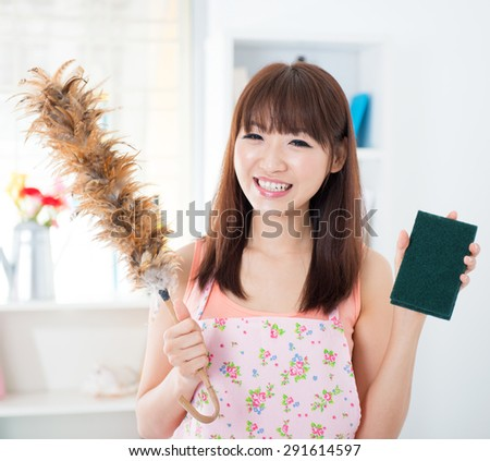 Happy Asian housewife with apron housecleaning, hand holding duster and cleaning sponge. Young woman indoors living lifestyle at home. - stock photo