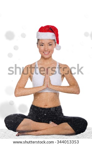 happy asian in christmas cap with snow practicing yoga isolated on white - stock photo