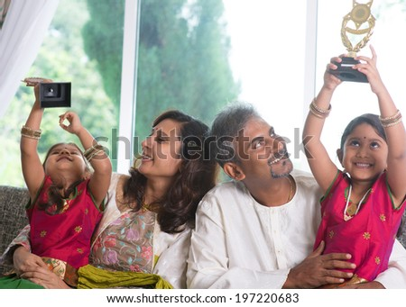 Happy Asian Indian family at home. Kid raised their trophy high up, education achievement concept. Parents and children indoor lifestyle. - stock photo