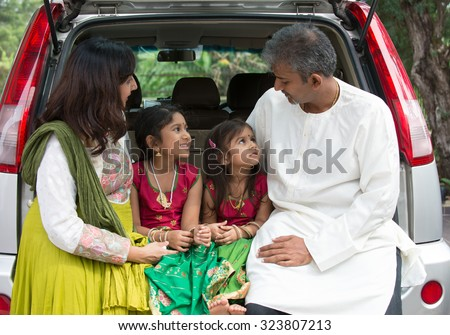 Happy Asian Indian family sitting in car talking and smiling happily - stock photo