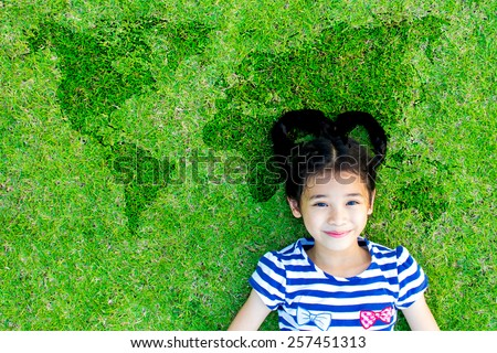 Happy Asian kid with heart-shaped hair lying on grass floor with world map background : Earth day with happy child : Save the planet concept : Children day and world environment day concept - stock photo