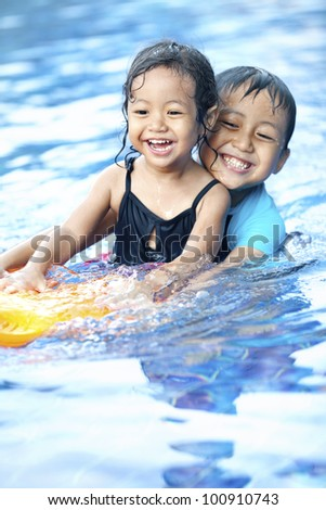 Happy Asian kids having fun at swimming pool during summer - stock photo
