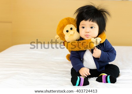 Happy asian little girl 7 month with playing with monkey doll - stock photo