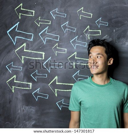 Happy Asian man standing in front of a dark chalkboard with arrow signs drawn pointing. - stock photo