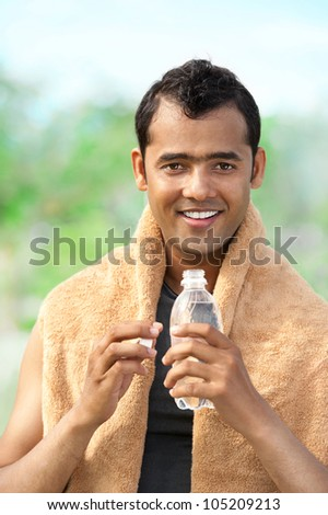 Happy Asian man with plastic bottle looking at camera - stock photo