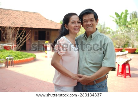 Happy Asian mature couple in the backyard of their house - stock photo