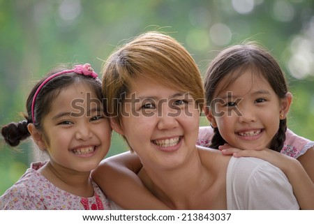 Happy Asian mother and daughter enjoying their time in the park - stock photo