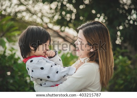 Happy asian mother playing with her son in the park - stock photo