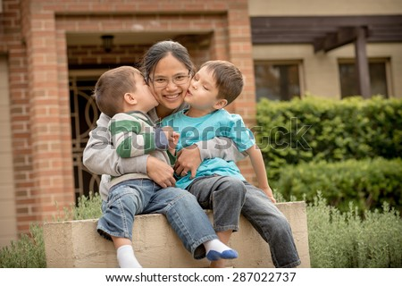 Happy Asian mother with her 2 boys (2 and 5 years old) in front of their new suburban home  - stock photo